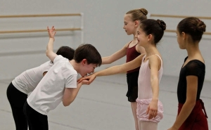 Jane Cohen, 10, center, breaks into nervous giggles after Aidan Duffy, 9, kissed her hand during rehearsals for Pennsylvania Ballet's The Nutcracker (photo by Michael Bryant) 2013